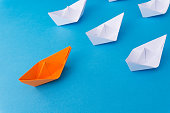 Business Leadership Concept - Colored Color Paper ship Origami leading the rest of the white paper ship on blue background.