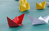 Leadership concept red leader paper boat standing out from the crowd of yellow boats