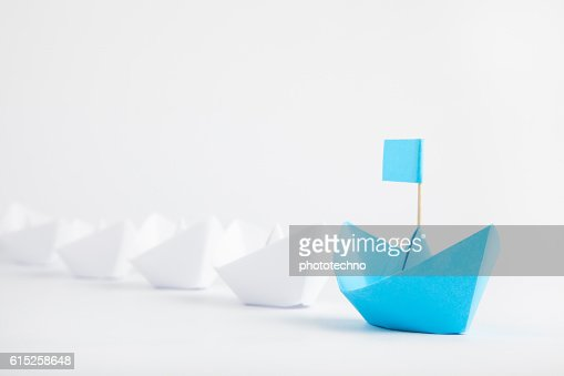 Leadership concept with blue paper ship leading among white : Stock Photo