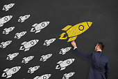 Leadership concept with rocket on chalkboard background