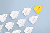 Leadership concepts with yellow paper airplane leading among white