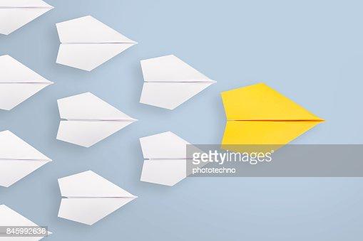 Conceptos de liderazgo con líder del avión de papel amarillo entre blanco : Foto de stock