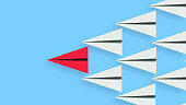 Leadership illustration concept of a red paper plane leading a team of followers. Clipping path included for easy selection.