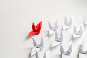 red paper bird leading white ones, leadership concept