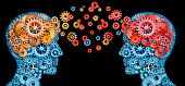 Teamwork and Leadership with education symbol represented by two human heads shaped with gears with red and gold brain idea made of  cogs representing the concept of intellectual communication through