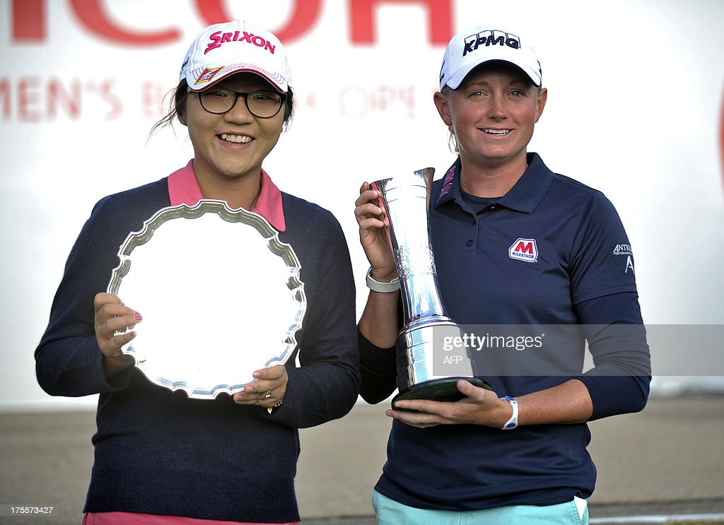 Leading amateur New Zealand's Lydia Ko (L) stands next to winner, US golfer Stacy Lewis after their successes at the Women's British Open Golf Championship at the Old Course in St Andrews, Scotland, on August 4, 2013. US golfer Stacy Lewis won the women's British Open on Sunday by two shots. Lewis, the winner of the 2011 Kraft Nabisco Championship, collected her second major with a final round 72 for an eight-under-par total of 280. AFP PHOTO/ANDY BUCHANAN