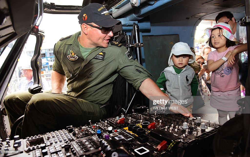 Leading Seaman Stephen McGreal of the HMAS Darwin shows children around the ship's helicopter at Royal Australian Navy's Sydney base of Garden Island during an open day after the Navy celebrated 100 years since their first ships entered Sydney Harbour, on October 7, 2013. The open day followed the Royal Australian Navy International Fleet Review which also included visiting warships from Britain, Singapore, Japan, India, Thailand and the United States. AFP PHOTO/William WEST