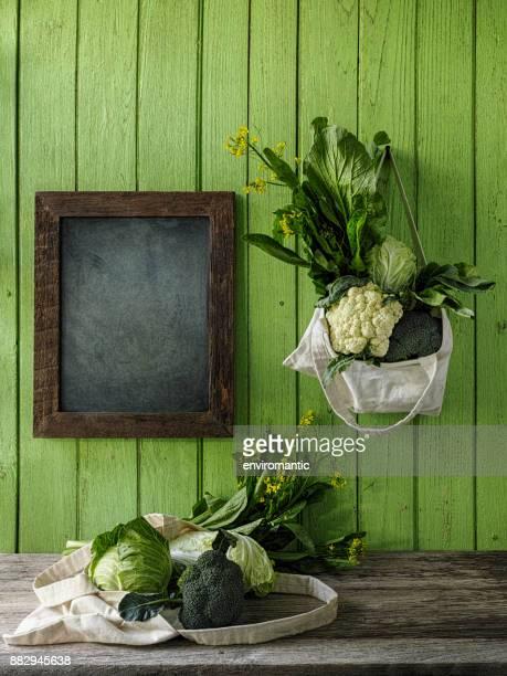 緑豊かな緑の野菜は、野菜の下に木製のテーブルの別の袋で古いの緑の木の板の壁背景に、黒板の側で再利用可能なコットン バッグにぶら下がっています。