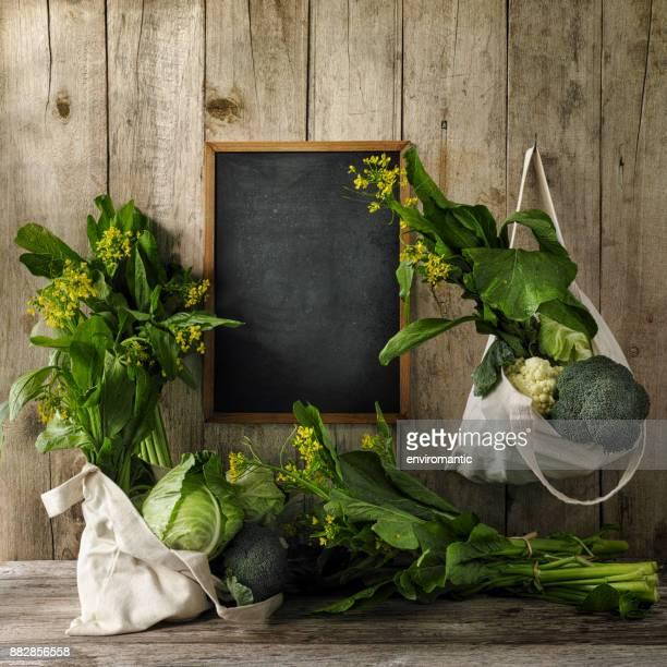 古い木板壁バック グラウンドに、黒板の横に、釘から再利用可能なコットン バッグにぶら下がっている緑の葉野菜。側と木のテーブルの下より多くの野菜です。