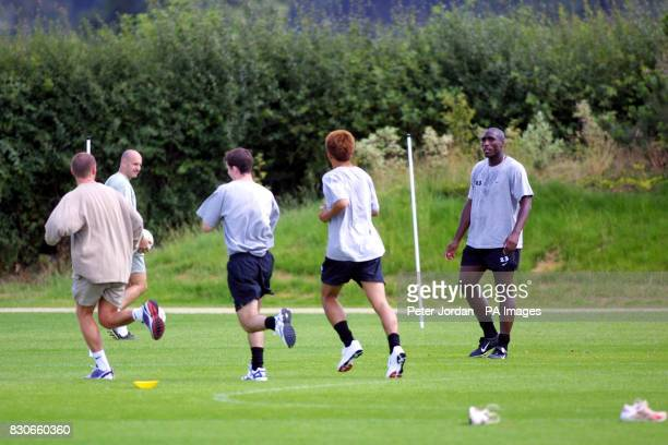 Arsenal's Sol Campbell watches new signing Junichi Inamoto as he jogs with teammates during a training session at London Colney Hertfordshire