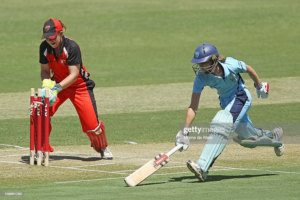 Leah Poulton of the Breakers makes her ground as Tegan McPharlin of the Scorpions breaks the bails during the women's twenty20 match between the South Australia Scorpions and the New South Wales Breakers at Adelaide Oval on December 23, 2012 in Adelaide, Australia.