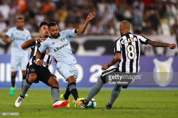 Leandrinho and Bruno Silva of Botafogo struggle for the ball with Fernandinho of Gremio during a match between Botafogo and Gremio as part of...