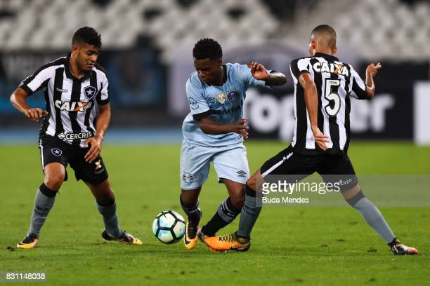 Leandrinho and Matheus Fernandes of Botafogo struggle for the ball with Lincoln of Gremio during a match between Botafogo and Gremio as part of...