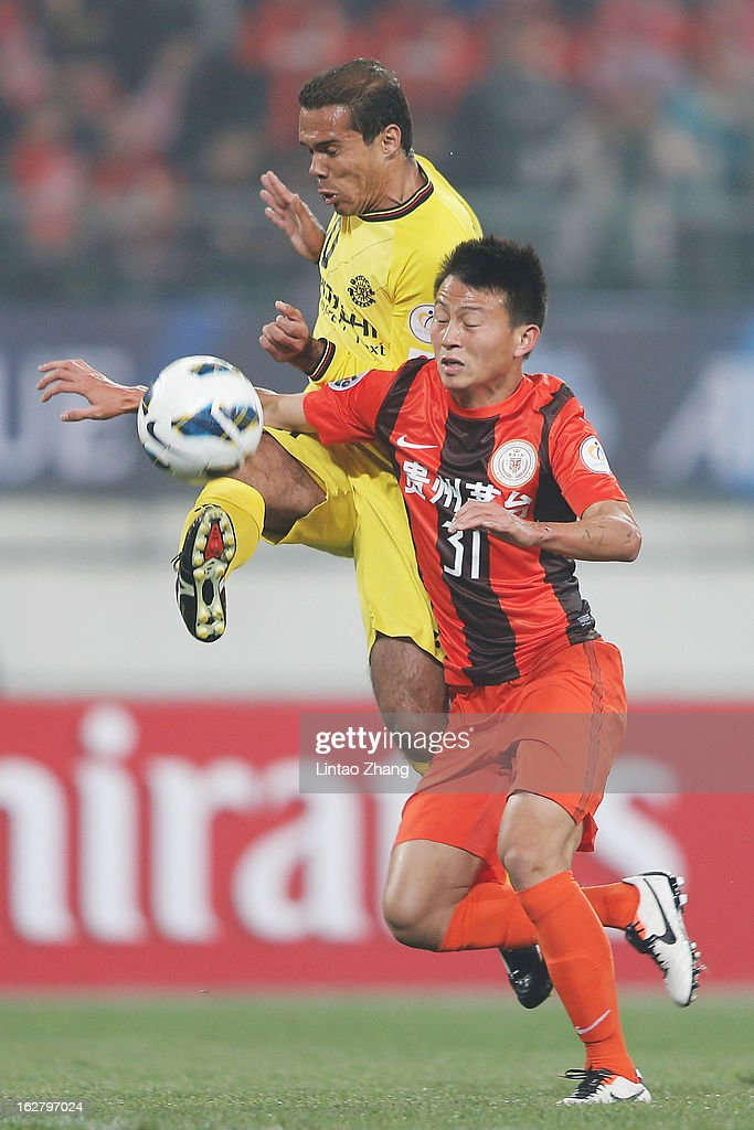 Leandro Domingues (L) of Kashiwa Reysol controls the ball with Rao Weihui of Guizhou Renhe during the AFC Champions League match between Guizhou Renhe and Kashiwa Reysol at Olympic Sports Center on February 27, 2013 in Guiyang, China.