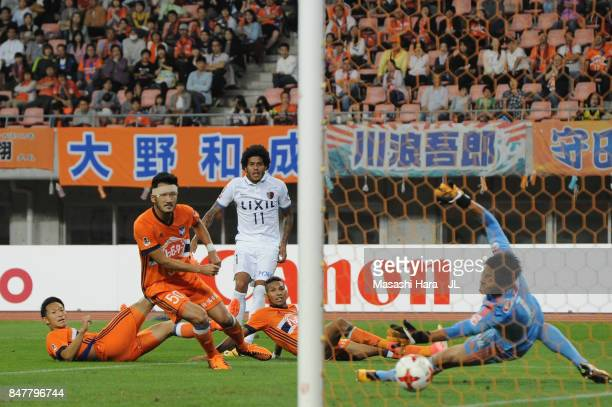 Leandro of Kashima Antlers scores his side's third and hat trick goal past Koki Otani of Albirex Niigata during the JLeague J1 match between Albirex...
