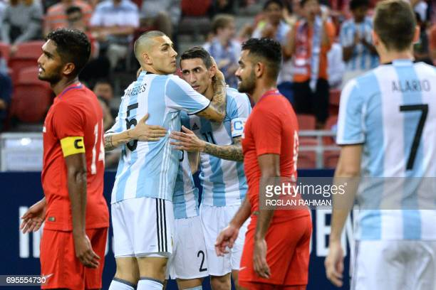 Leandro Paredes of Argentina celebrates with teammate Angel Di Maria after scoring a goal against Singapore during their international friendly...