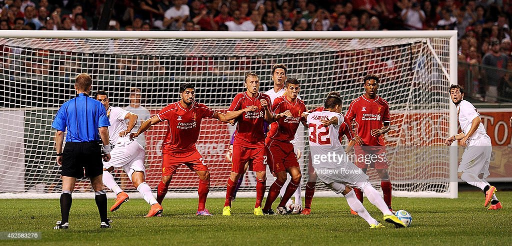 Leandro Paredes of AS Roma takes a free kick as Emer Can, Lucas Leiva, Conor Coady and Jordon Ibe of Liverpool during the pre-season friendly match between Liverpool FC and AS Roma at Fenway Park on July 23, 2014 in Boston, Massachusetts.