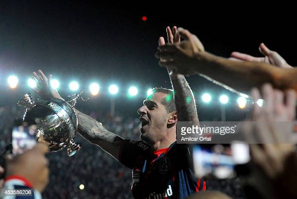 Leandro Romagnoli of San Lorenzo celebrates with the trophy after a second leg final match between San Lorenzo and Nacional as part of Copa...