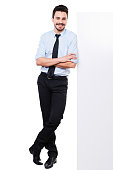 Full length of handsome young man in shirt and tie leaning at the copy space and keeping arms crossed while standing against white background