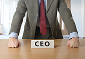CEO leaning on desk in an office