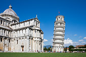 Leaning Tower of Pisa and Pisa Cathedral in Italy with unrecognizable tourists for scale.  Concepts could include architecture, travel, European history, others.