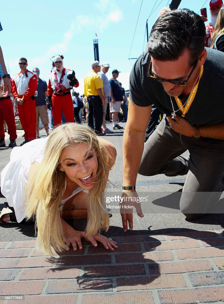 LeAnn Rimes and Eddie Cibrian react after kissing the bricks at the 2014 Indy 500 at Indianapolis Motorspeedway on May 25 2014 in Indianapolis Indiana
