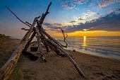 The sun sets behind a leanto built from driftwood on a a sandy beach in Pinery Provincial Park - Ontario, Canada