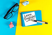 Learn english - note at blue and yellow background with teachers glasses.