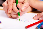 Child hand with pencil and woman hand helping to write letters