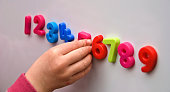 A young child learns 1 to 9 with multicoloured magentic numbers on a white board.