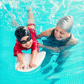 Cheerful boy learning to swim with swimming board