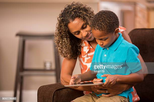 Learning with mom! African descent mother, child and digital tablet.