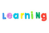 Learning written in magnetic letters. on a white studio background.