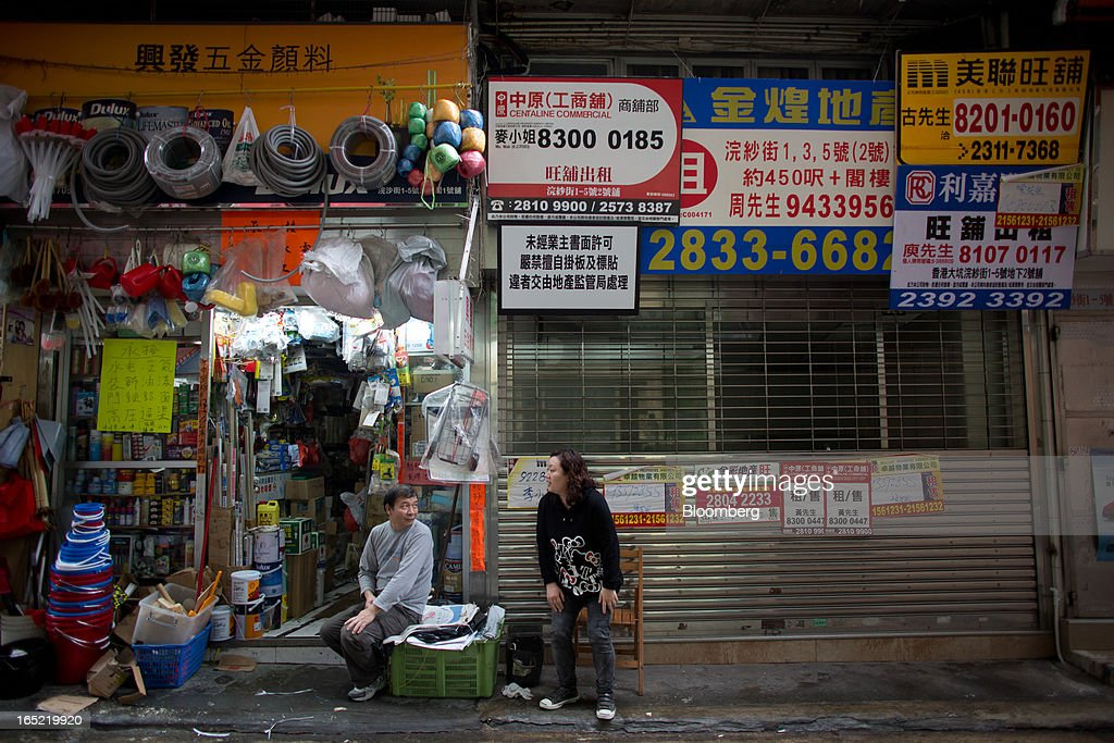 Lease advertisements adorn the front of a shuttered commercial space next to a hardware store as vendors sit and chat in the Tai Hang area of Hong Kong, China, on Saturday, March 30, 2013. Rents are climbing in neighborhoods near Causeway Bay and Hong Kong's other prime shopping districts, known for luxury stores that attract free-spending tourists from mainland China. That's squeezing out mom-and-pop shops, congee and noodle vendors as developers and landlords seek to profit from the trend. Photographer: Lam Yik Fei/Bloomberg via Getty Images