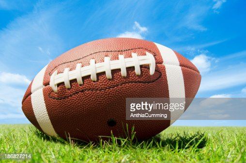 Leather american football on grass pitch with blue sky