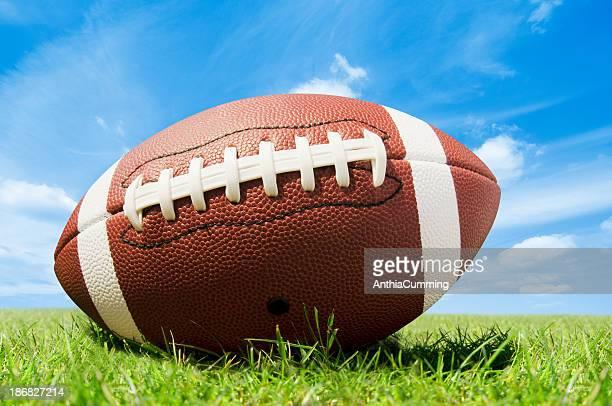 Leder-american-football auf Gras Feld mit blauem Himmel