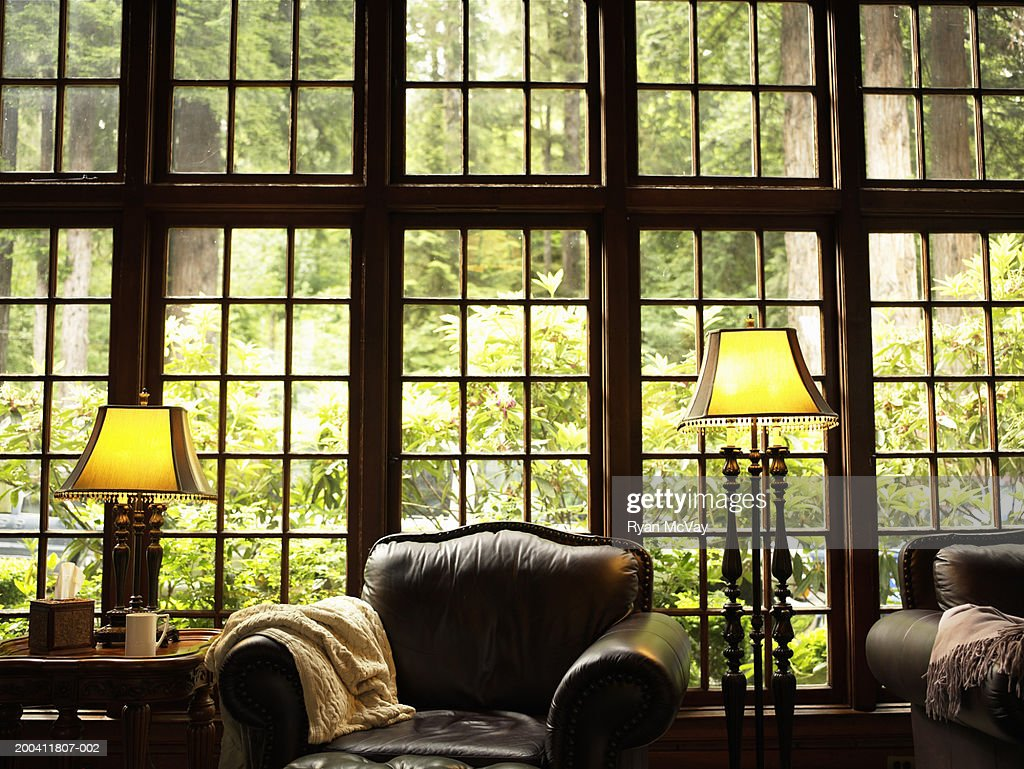 Leather armchair, lamps and side table in lobby of lodge : Stock Photo