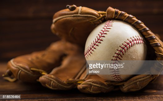 Leather baseball glove and ball on a wooden bench : Stock Photo