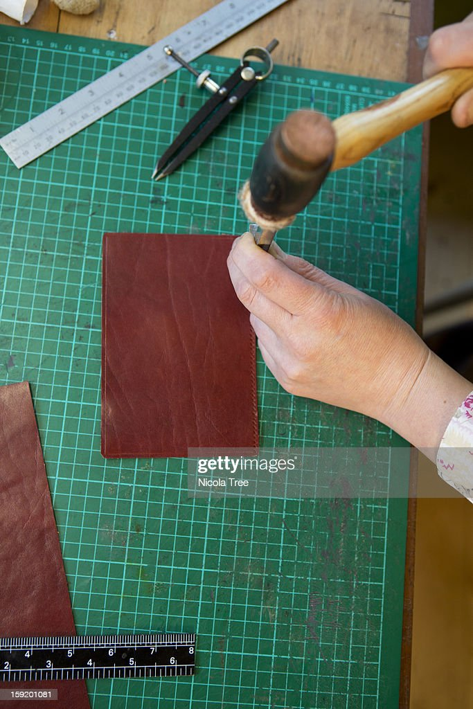 Leather designer working on a pice of leather : Stock Photo