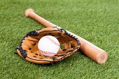 Leather Glove With Baseball And Bat On Green Pitch