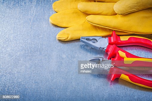 Leather safety gloves pliers wire-cutter on metallic background : Stock Photo