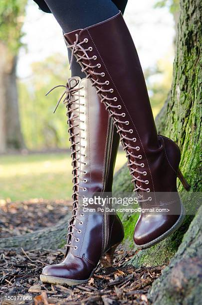 Leather stiletto boots leaning on tree