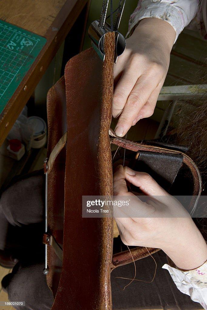 Leather stitcher fixing a satchel : Stock Photo