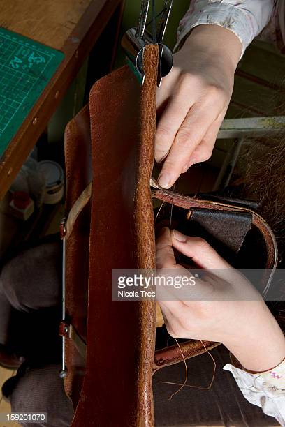 Leather stitcher fixing a satchel