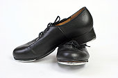A pair of black, leather tap dancing shoes.