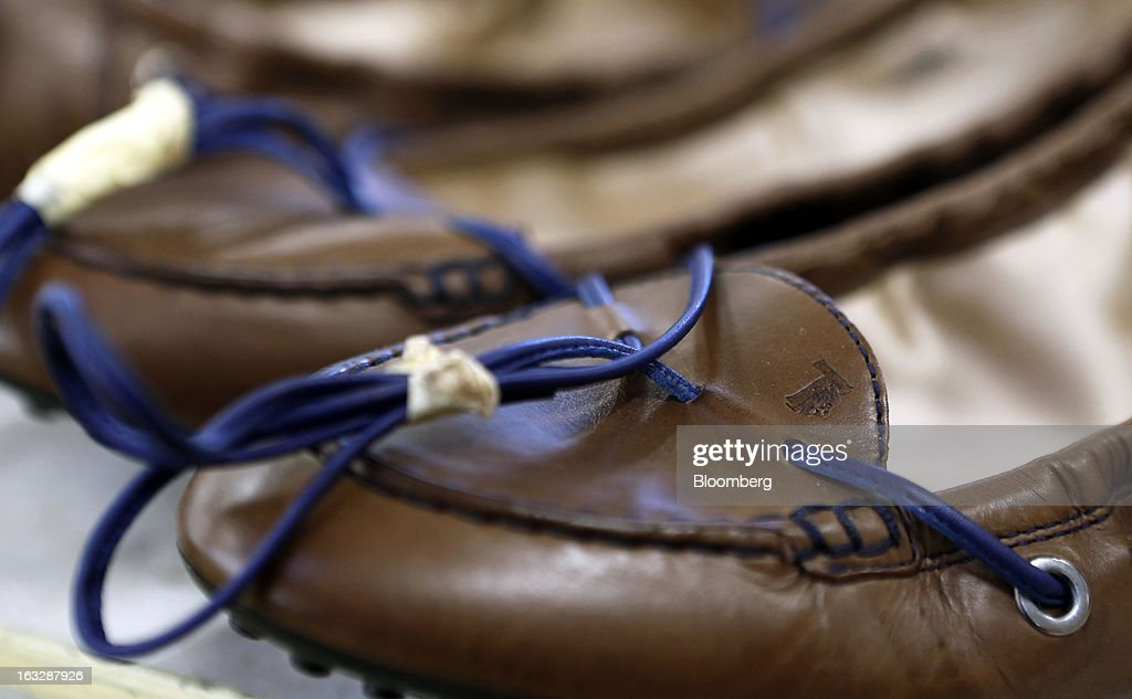 Leather ties sit bound on newly-manufactured leather shoes ahead of shipping at Tod's SpA's headquarters in Sant'Elpidio a Mare, near Civitanova Marche, Italy, on Wednesday, March 6, 2013. Tod's, the maker of luxury footware and clothing accessories, is due to report earnings for 2012 on March 13. Photographer: Alessia Pierdomenico/Bloomberg via Getty Images