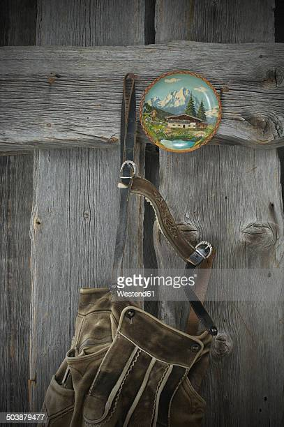 Leather trousers and painted wooden plate hanging on wooden wall