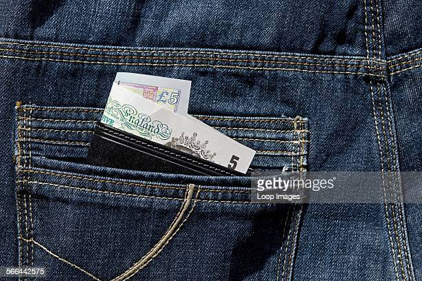 Leather wallet showing English banknotes in the back pocket of jeans