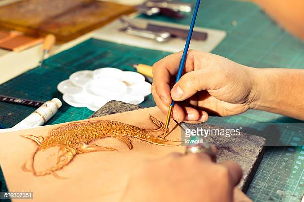 leatherworker painting fish pattern on leather