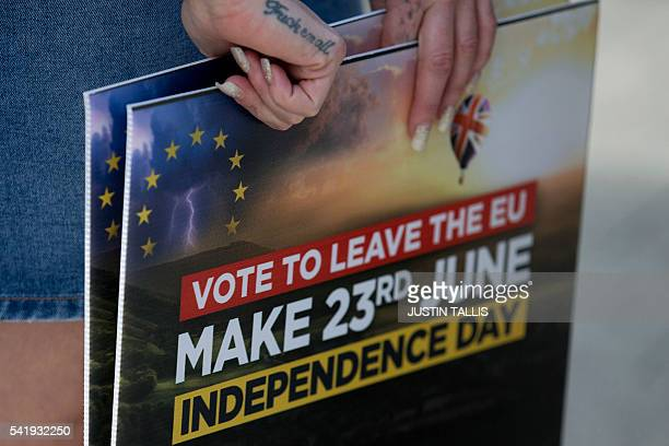 A Leave campaigner holds placards as she waits for the arrival of UK Independence Party leader Nigel Farage in ClactononSea eastern England on June...